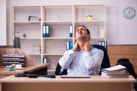 Young male employee suffering from osteochondrosis at workplace Stockfoto