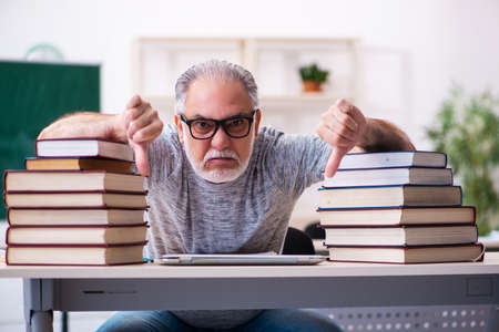 Old male student being exhausted during exam preparation