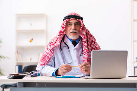 Old male arab doctor working in the clinic