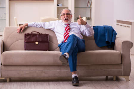Old male boss employee coming home from work Imagens