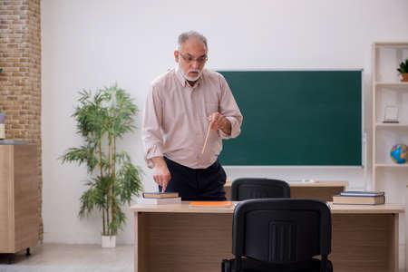 Old male teacher in front of blackboard 版權商用圖片