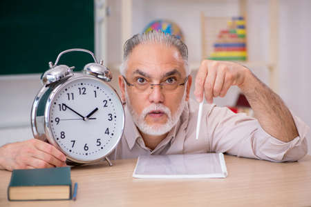 Old male teacher in time management concept