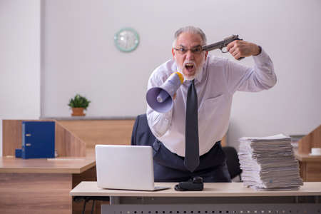 Old male employee being desperate with excessive work in the off