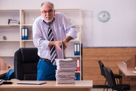Old male employee unhappy with excessive work in the office