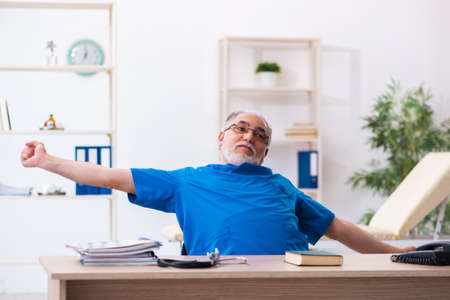 Old male doctor extremely tired after night shift