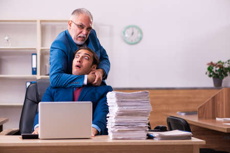 Old male boss and his young male assistant in bullying concept