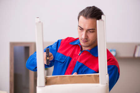 Young male contractor repairing chair indoors