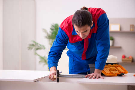 Young male contractor repairing table indoors