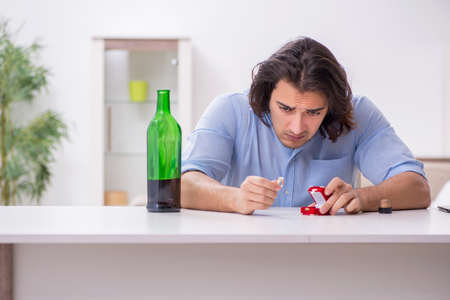 Young male alcoholic in unrequited love concept Imagens