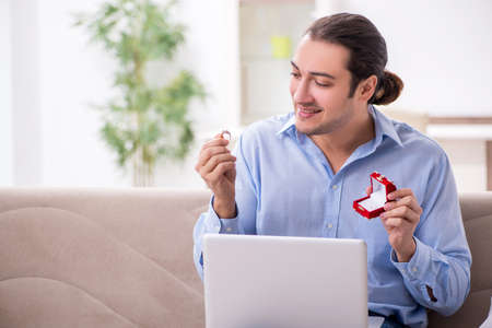 Young man doing marriage proposal via Internet