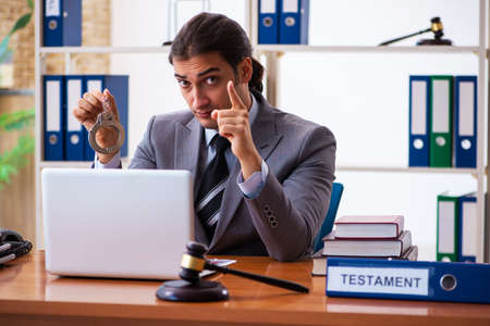 Young male lawyer sitting in the office Imagens