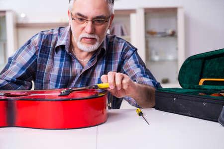 Senior repairman repairing musical instruments at home