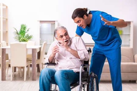 Old man in wheel-chair and bad caregiver indoors