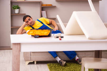 Young male contractor repairing chair at home