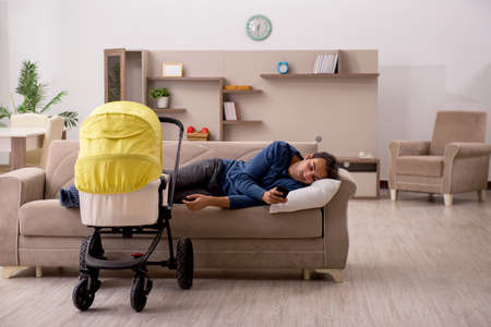 Young male contractor looking after baby at home