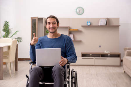 Young man in wheel-chair suffering at home