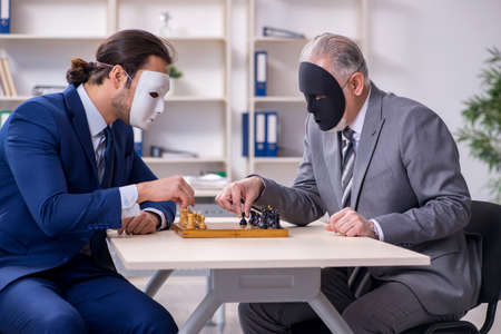 Two businessmen playing chess wearing masks