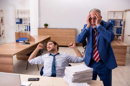 Young male employee and old boss burning papers at workplace Imagens