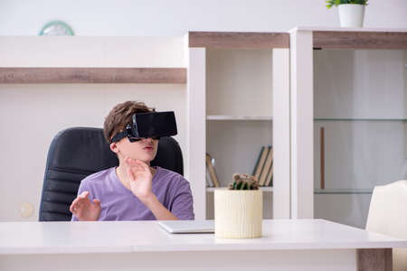 Schoolboy wearing virtual glasses at home