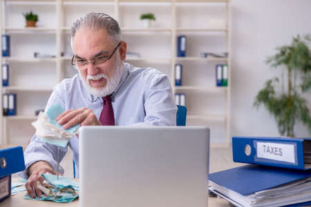 Old male accountant in budget planning concept in the office