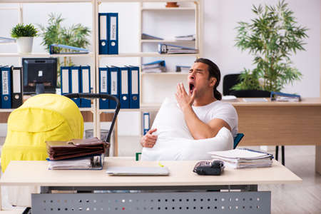 Young male employee looking after newborn at workplace