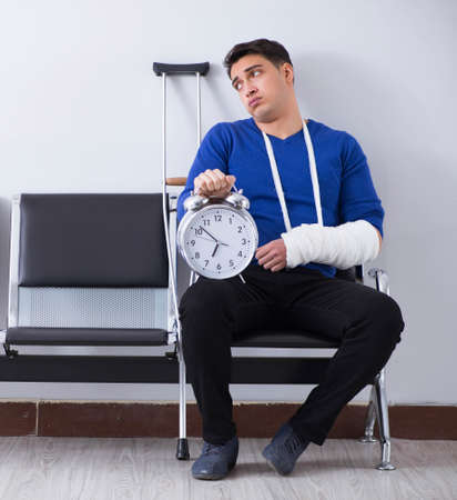 Desperate man waiting for his appointment in hospital with broke Stock Photo