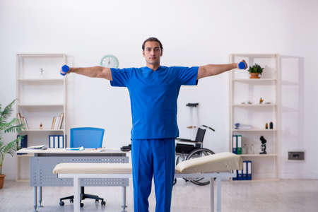 Young male doctor physiotherapist doing sport exercises Standard-Bild