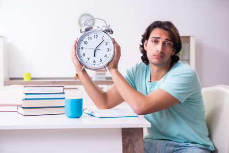 Young male student preparing for exams in time management concept