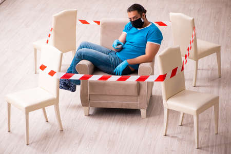 Young man watching tv at home in pandemic concept