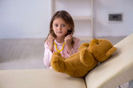 Small girl holding bear toy waiting for doctor in the clinic
