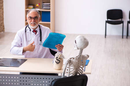 Old male doctor cardiologist and skeleton patient