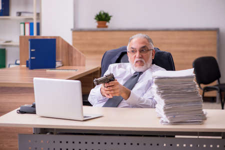 Old male employee being desperate with excessive work in the office