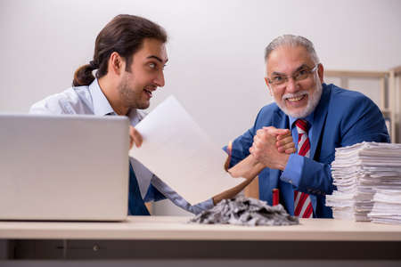 Young male employee and old boss burning papers at workplace