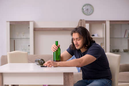 Young unemployed man drinking alcohol at home