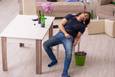 Young alcohol addicted man suffering from stomachache at home