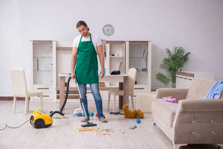 Young male contractor cleaning the flat after kids party