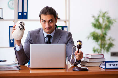 Young male lawyer sitting in the office