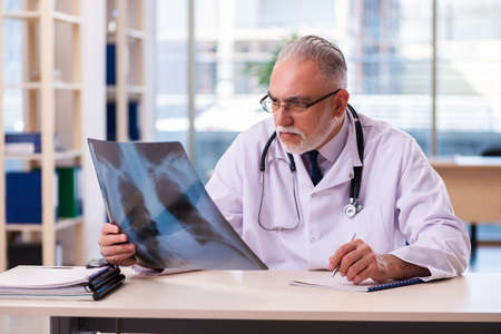 Old male doctor radiologist working in the clinic