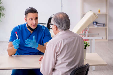 Old patient visiting young male doctor in blood sampling concept