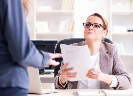Angry boss dismissing employee for bad underperformance Stock Photo