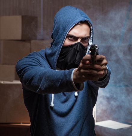 Aggressive manwith gun wearing face mask