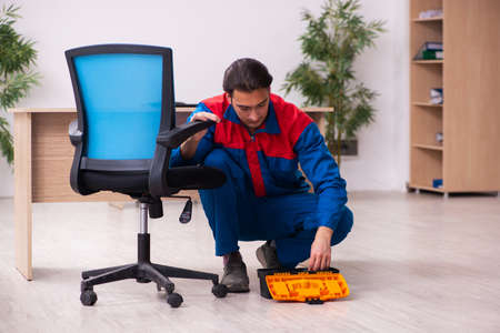 Young male contractor repairing furniture in the office