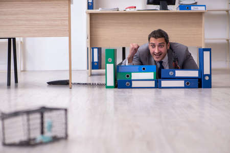 Young male employee and mousetrap in the office