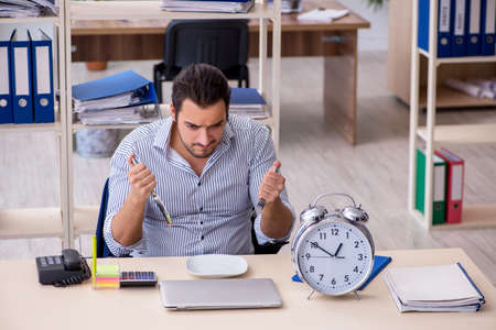 Hungry male employee waiting for food in time management concept