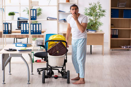 Young male employee looking after newborn at workplace Standard-Bild