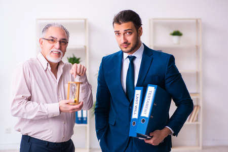 Young male lawyer and old man in testament and time management c