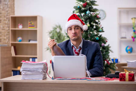 Young male employee celebrating new year in the office