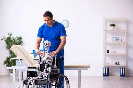 Young male doctor and skeleton in wheel-chair Zdjęcie Seryjne