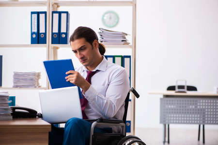 Young male employee after accident in wheel-chair at workplace