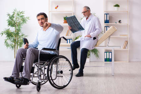 Young man in wheel-chair and old doctor radiologist Zdjęcie Seryjne